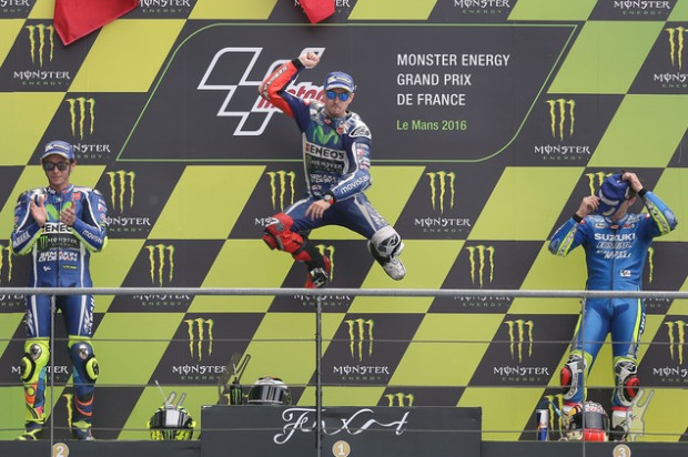 Yamaha's MotoGP rider Jorge Lorenzo of Spain jumps on the podium to celebrate his victory of the French Grand Prix, in Le Mans, western France, Sunday, May 8, 2016. Italian rider Valentino Rossi placed second, left, and Maverick Vinales of Spain placed third. (AP Photo/David Vincent)